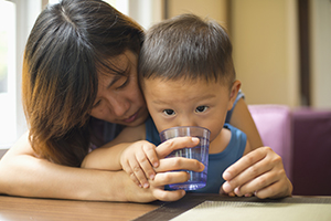Woman giving baby water to drink.