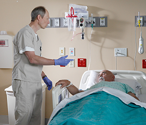 Healthcare provider talking to man in hospital bed.