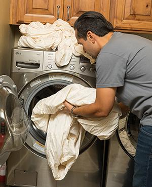 Man putting sheets in washing machine. in washing machine.