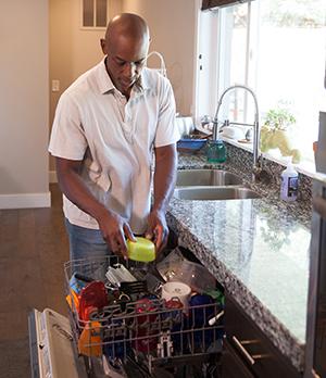 Man loading dishwasher.