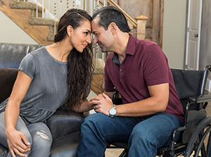 Man in wheelchair and woman on couch talking in living room.