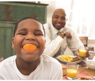 Child with orange in his mouth, with his father smiling in the background