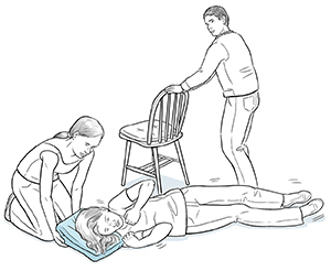 Woman placing pillow under head of woman having a seizure, man moving chair out of the way.