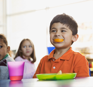 Young boy at school lunch table with orange in his mouth