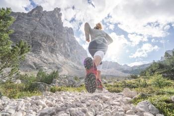 Woman running along a mountain trail