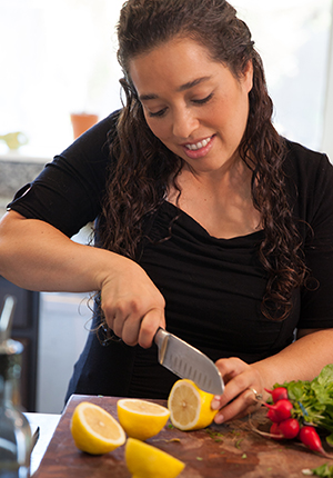 Woman chopping fresh vegetables in kitchen.