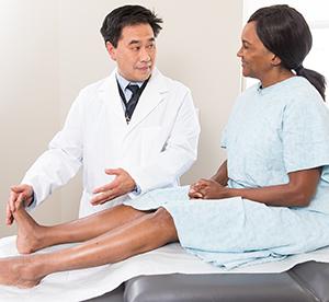 Healthcare provider examining woman's foot.