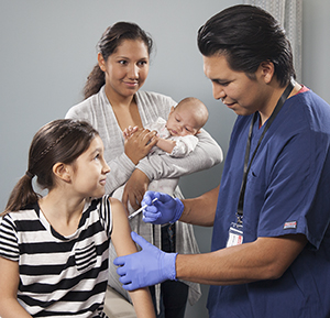 Healthcare provider giving girl injection in arm while woman with baby looks on.