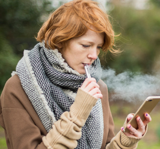 Young woman vaping and looking at her phone