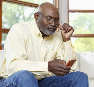 Older man, seated, looking at his cell phone