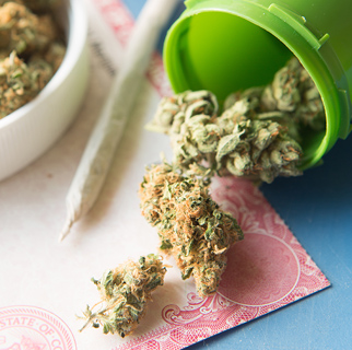 A rolled up marijuana cigarette as well as dried green leaves loosely spilled out from a canister.