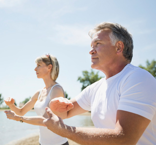 Man and woman doing tai chi outdoors