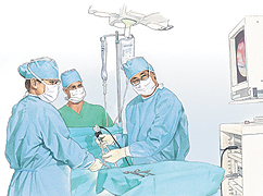 Three healthcare providers in surgical gowns, masks, and hats performing operation using laparoscope. They are looking at video monitor.
