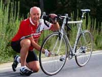 Photo of an older man adjusting his bicycle wheel