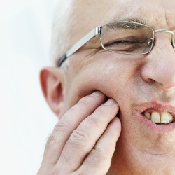 Man with expresion of pain holding his cheek