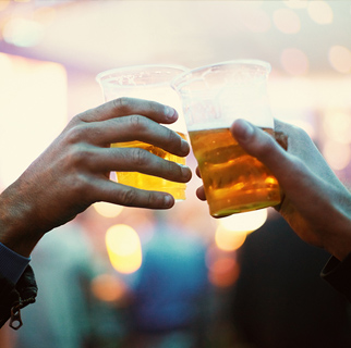 close up image of of two glasses of beer clinking together.