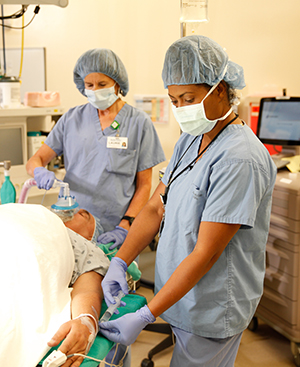 Healthcare providers in operating room preparing man for surgery.
