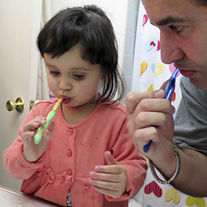 Man and toddler girl brushing teeth in bathroom.
