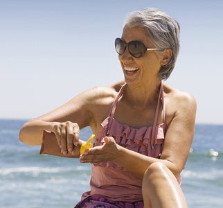 Older woman at the beach, with bottle of sunscreen