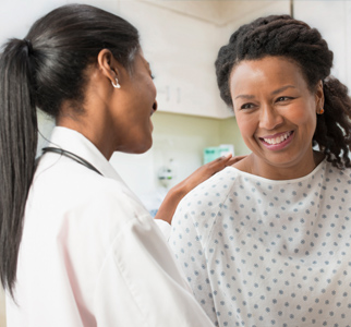 Healthcare provider talking with woman in hospital gown