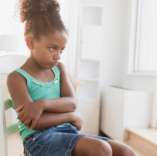 Little girl sitting in a chair with her arms crossed refusing to move.