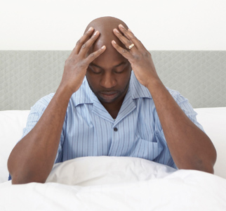 Man sitting up in bed, holding his head