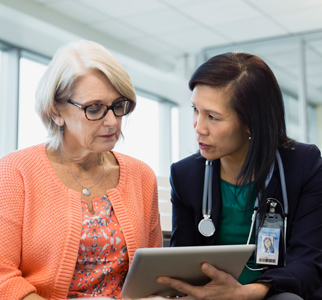 Female doctor talking with older female patient