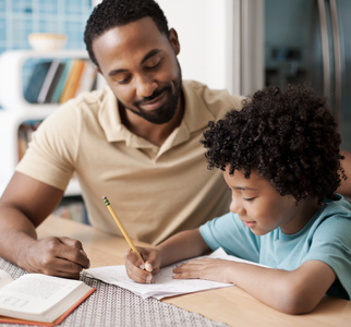 Man sitting at a kitchen table, watching his young son do homework