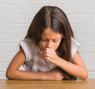Young girl with her head lowered, coughing
