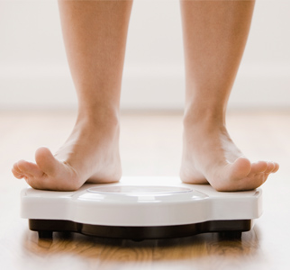 Bare feet standing on a bathroom scale