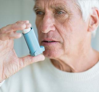 Older man preparing to use an inhaler