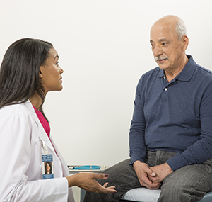 Man talking to healthcare provider in exam room.