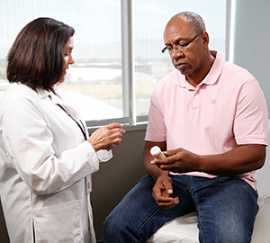 Healthcare provider talking to man in exam room.