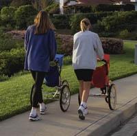 Dos madres caminando con cochecitos para correr