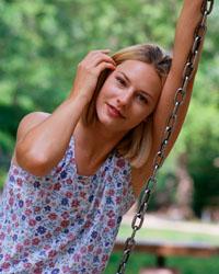 Imagen de una mujer joven sentada en un columpio