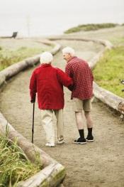 Pareja de ancianos caminando sobre una ruta