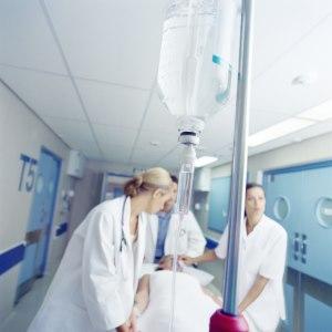 Imagen de un hombre llevado por el pasillo de un hospital en una camilla.