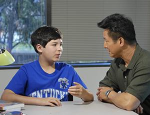 Un padre y su hijo hablan sentados a la mesa.