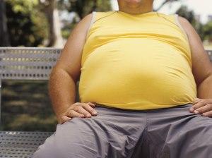 Vista del abdomen de un hombre que está sentado en el banco de un parque con una camisa amarilla.