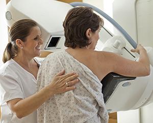 Una técnica ayudando a una mujer durante una mamografía