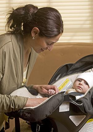 Mujer asegurando a un bebé en el portabebés.